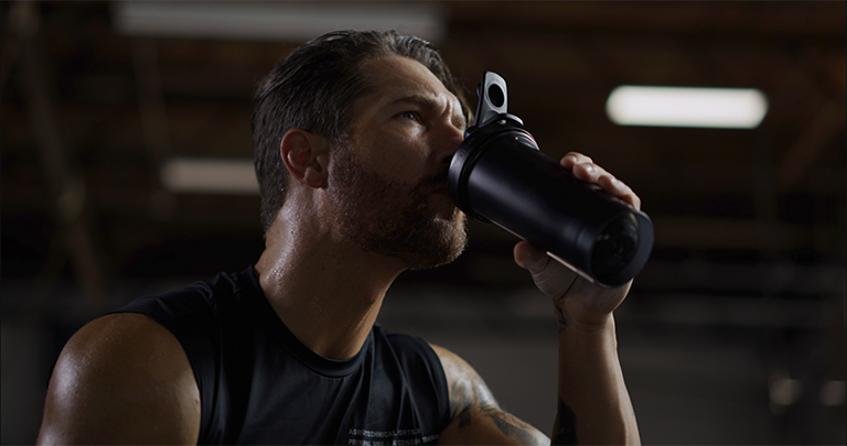 Man Drinking Water From a BlenderBottle Brand Shaker Cup