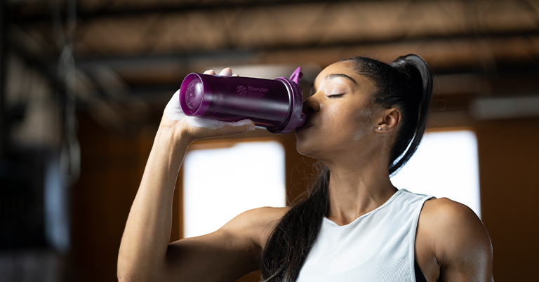 Woman drinking from a BlenderBottle Brand shaker cup.