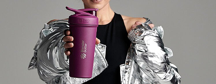 Woman holding the Strada Stainless Steel Shaker Bottle