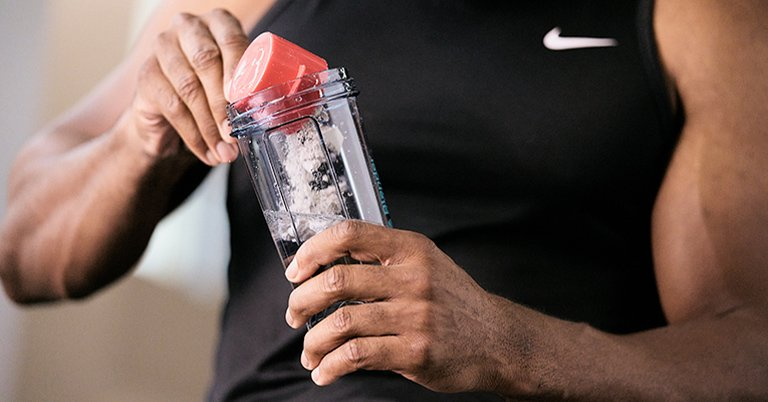 A man putting protein powder in a BlenderBottle brands protein shaker bottle to make a protein shake.