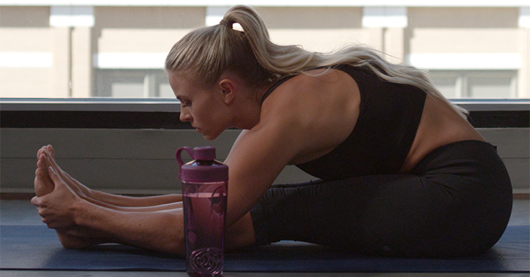 Woman Doing Yoga with BlenderBottle Brand Shaker Cup